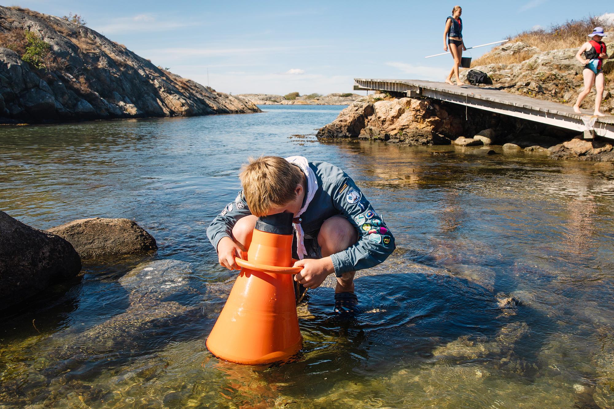 Scout undersöker vatten vid klippor;